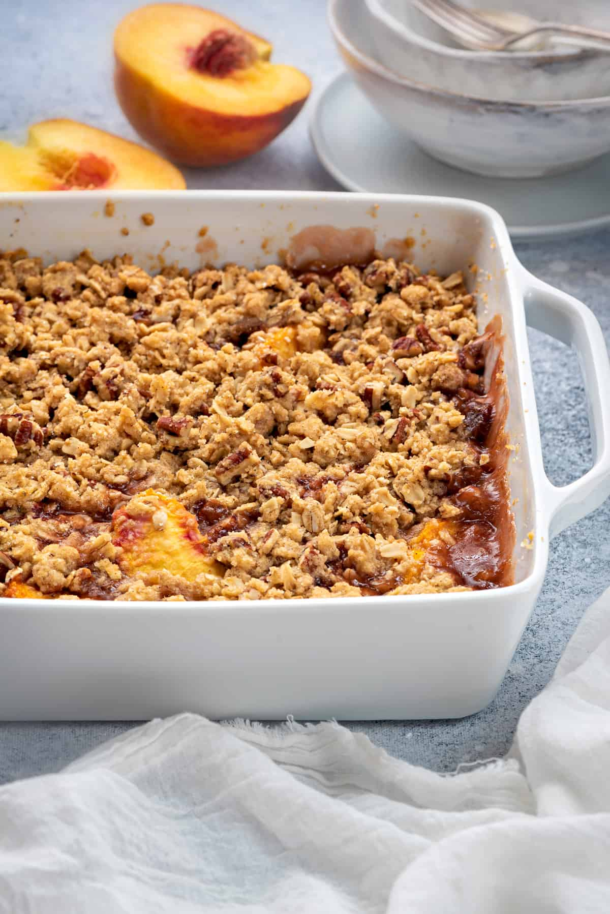healthy peach crisp with oat topping in a white casserole dish on a grey table