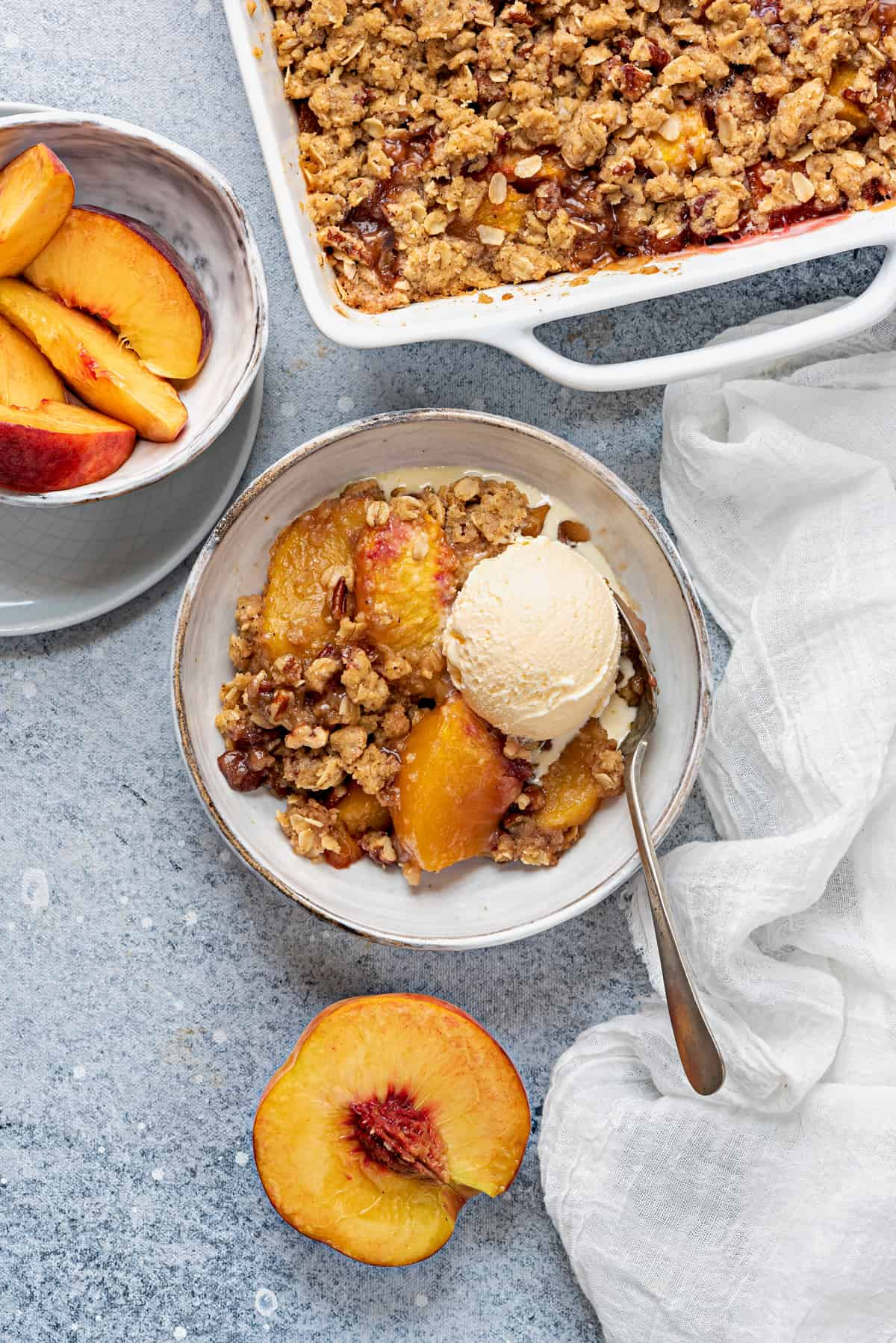 overhead shot of casserole dish, and a serving bowl of peach crisp with a scoop of ice cream