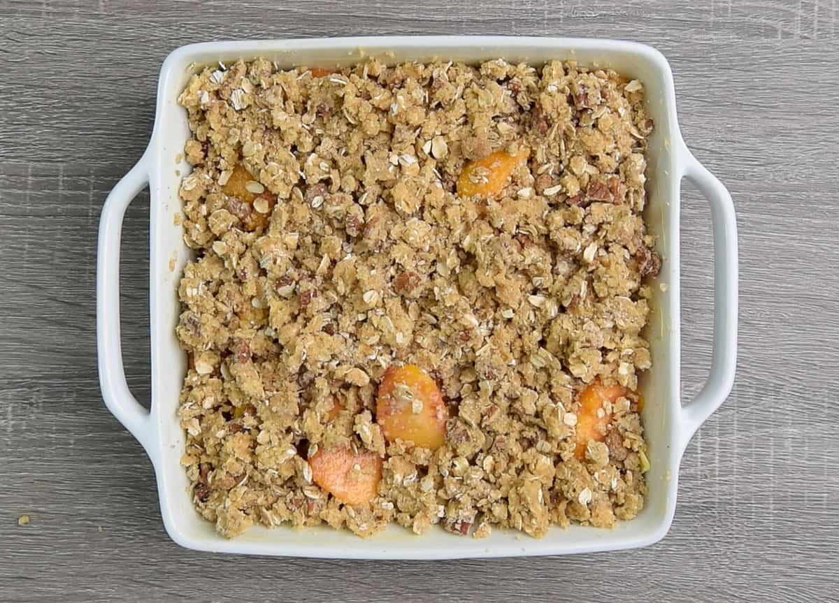 square white baking dish filled with unbaked peach crisp