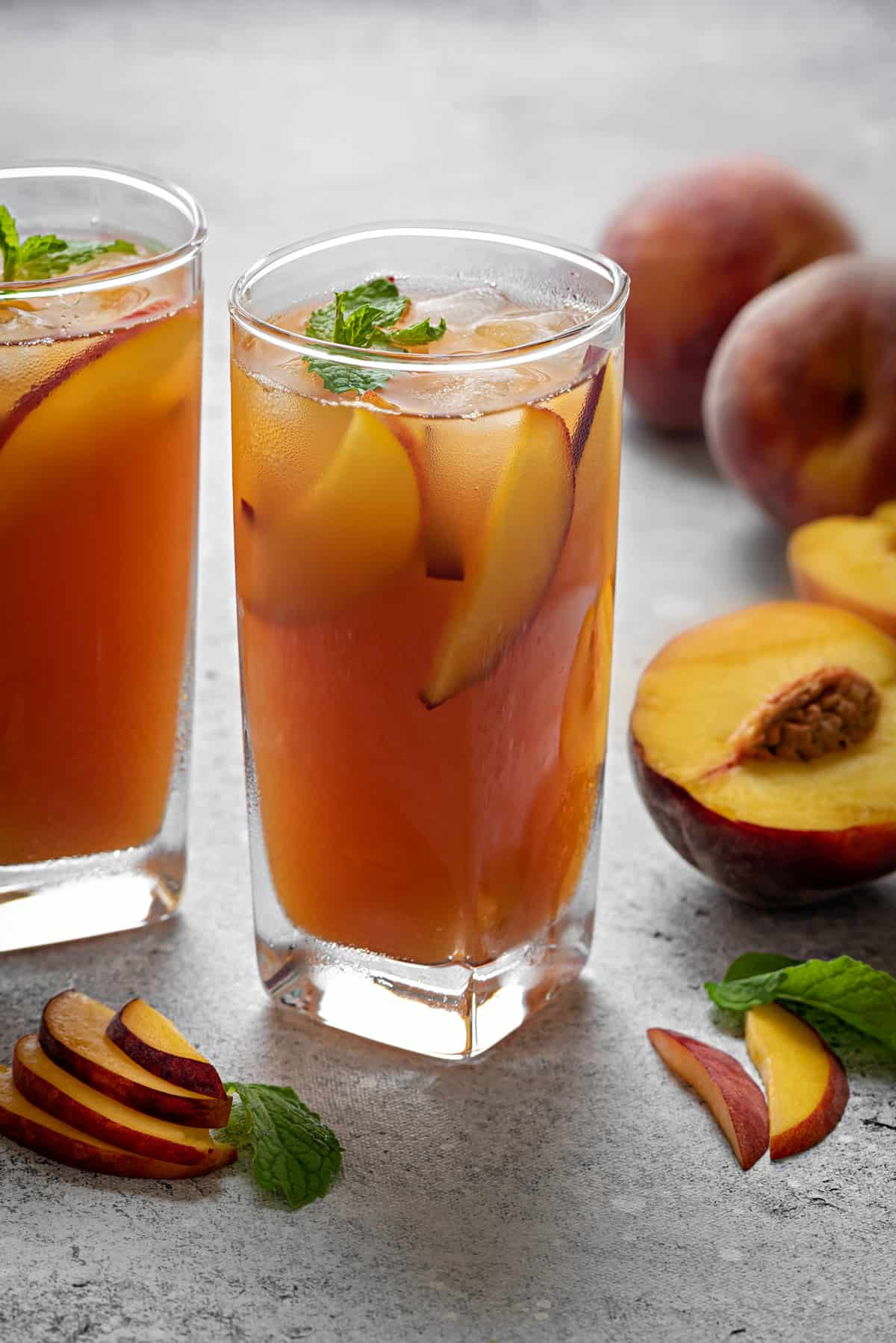 chilled sweet peach tea in two glasses with some sliced and whole peaches at the back