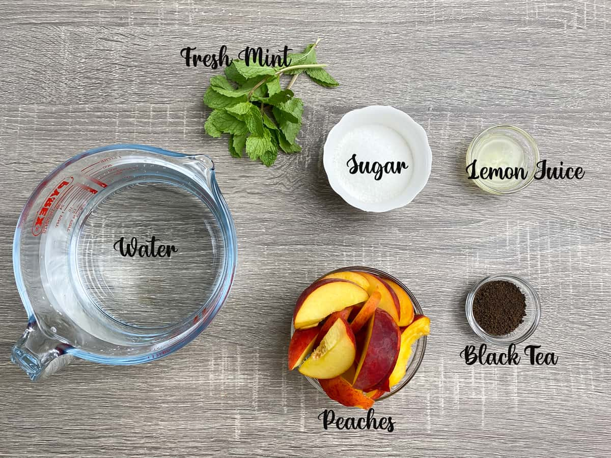 ingredients for peach iced tea measured in bowls and a jar on a grey table