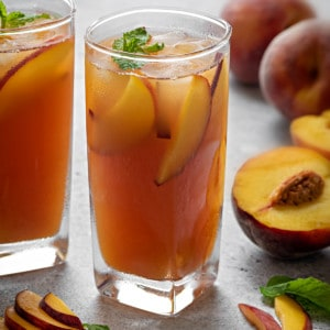 a tall glass with refreshing peach iced tea, peach slices and some fresh mint