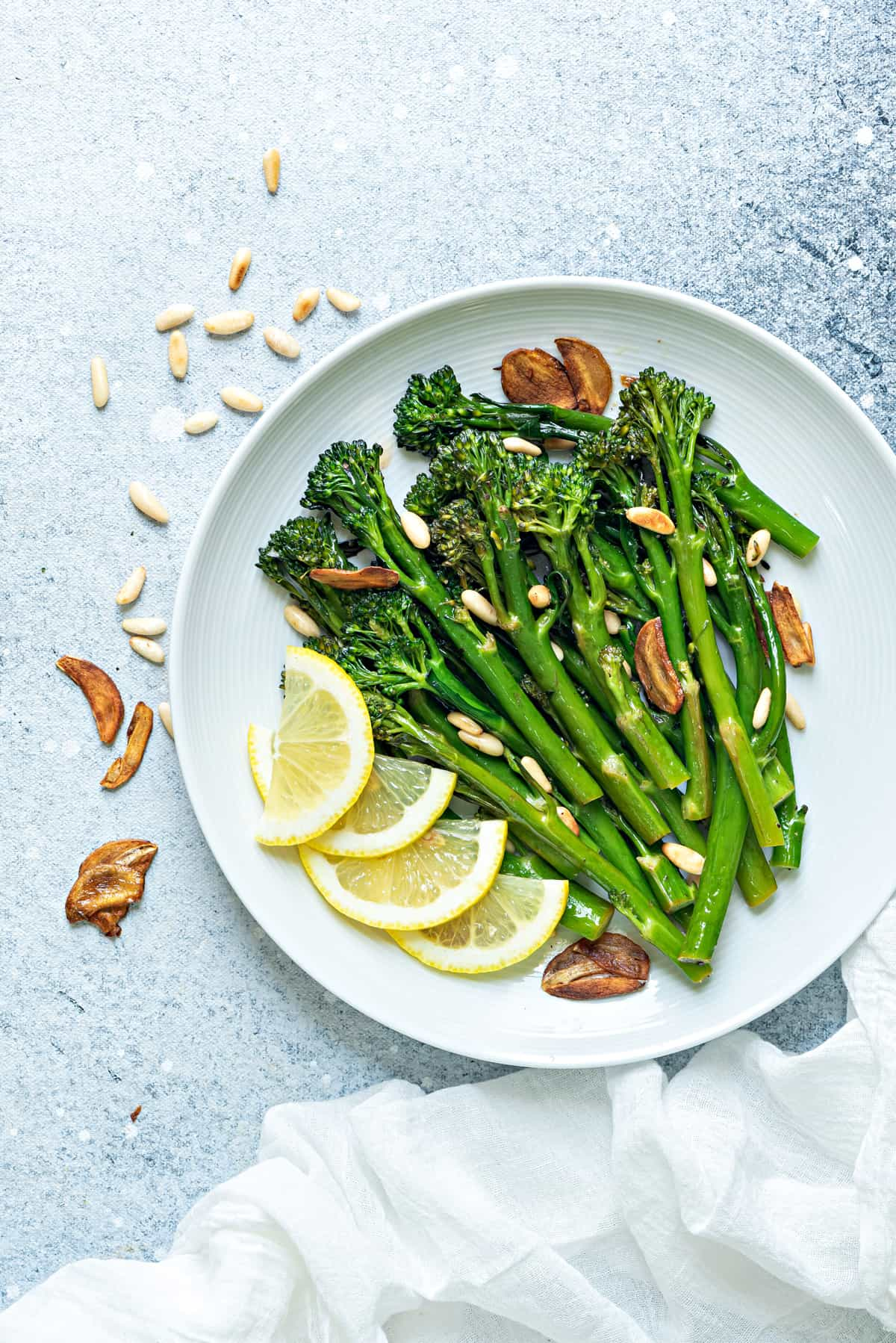 a serving platter of sautéed broccolini with fresh lemon slices, garlic chips and toasted pine nuts