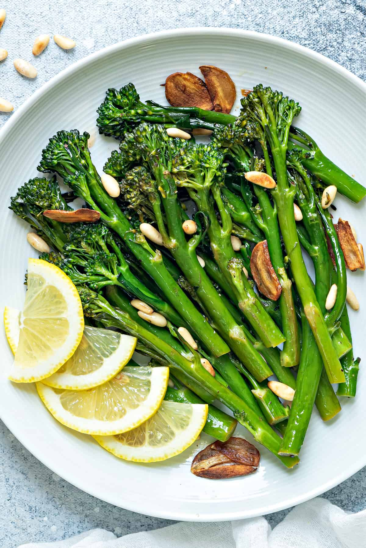 a round white plate of sautéed broccolini finished with garlic chips, pine nuts and lemon