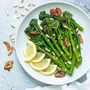 a round white plate of sautéed broccolini finished with garlic chips, toasted pine nuts and lemon