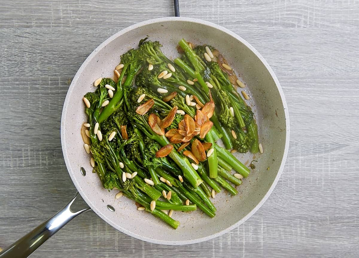 broccolini is cooked to al dente from pan frying and steaming, then finished with lemon juice, garlic chips and pignolias
