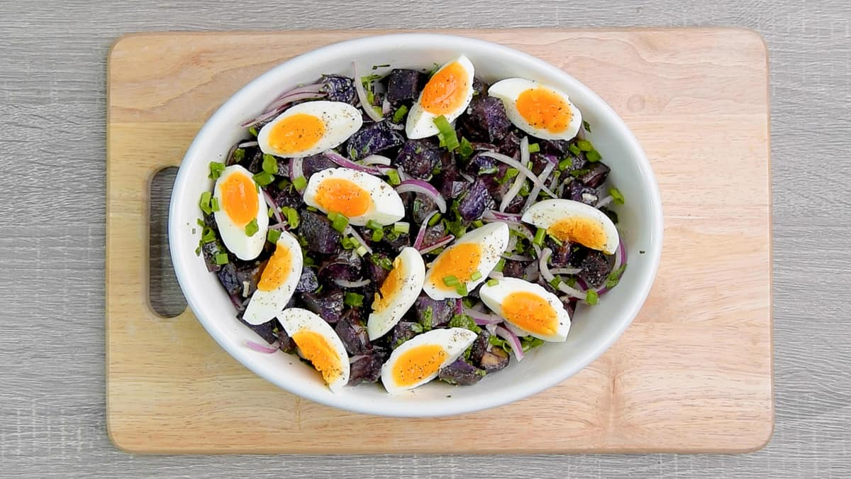 tossed purple potato salad in a serving bowl topped with wedges of jammy eggs