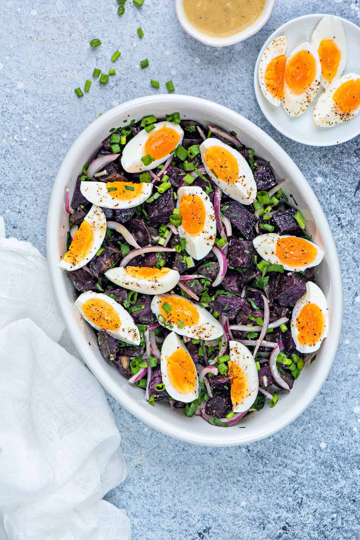 warm purple potato salad in white serving dish with a garnish of soft boiled eggs