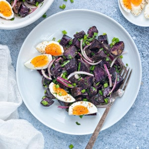 warm purple potato salad in a white plate with 7 minutes egg wedges and a silver fork